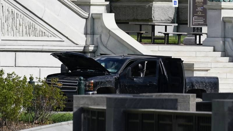 Authorities investigate a pickup truck parked on the sidewalk in front of the Library of...