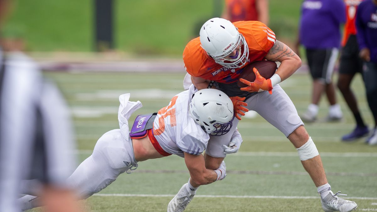 Hayden Bourgeois (left) tackles Tanner Ash after Ash made a catch in Saturday's first preseason scrimmage of Northwestern State's fall camp. Credit: Chris Reich/NSU Photographic Services