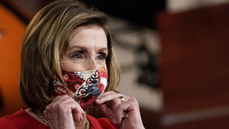 House Speaker Nancy Pelosi of California puts her mask back on after a news conference on...