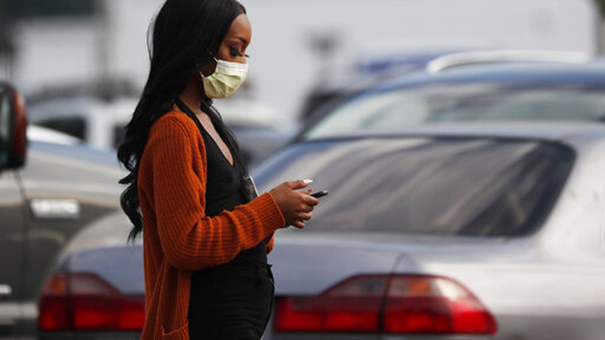 A shopper walks through the Target parking lot in northeast Jackson, Miss., Wednesday, April 8, 2020. The Mississippi Department of Health released figures today that show African Americans are being disproportionately affected by the coronavirus. (AP Photo/Rogelio V. Solis)