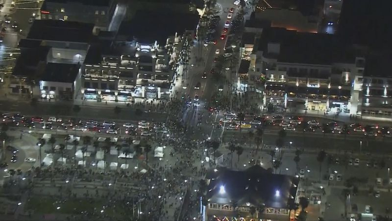This Saturday, May 22, 2021 aerial screenshot provided by FOX 11 KTTV shows people gathered at...
