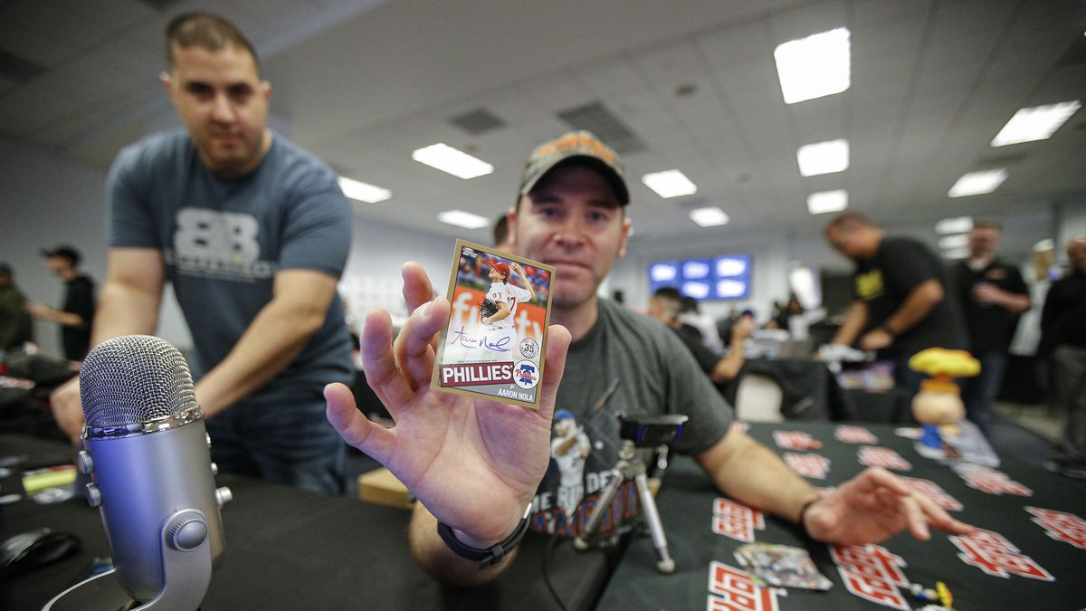 Bomber Sports Card breaker Chris Bame shows off an autographed Aaron Nola baseball card during the Topps Series 1 Million Card Rip Party Tuesday, Feb. 4, 2020 at AT&T Stadium in Arlington, Texas. (Brandon Wade/AP Images for Topps)