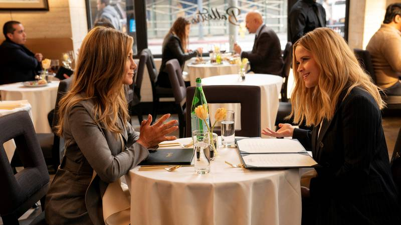 This image released by Apple TV+ shows Jennifer Aniston, left, and Reese Witherspoon in a scene...