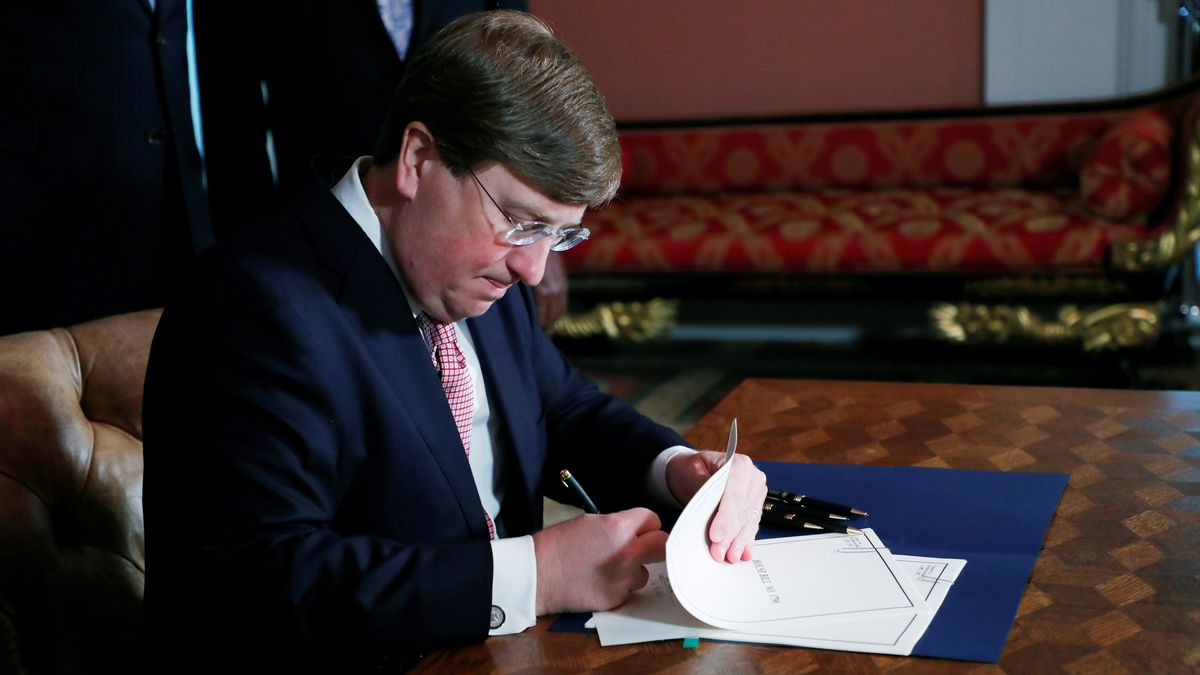 Mississippi Gov. Tate Reeves signs the bill retiring the last state flag with the Confederate battle emblem during a ceremony at the Governor's Mansion in Jackson, Miss., Tuesday, June 30, 2020. Upon signing the bill, the flag looses its official status.