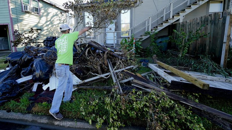Caleb Cormier moves debris after Hurricane Delta moved through, Saturday, Oct. 10, 2020, in...
