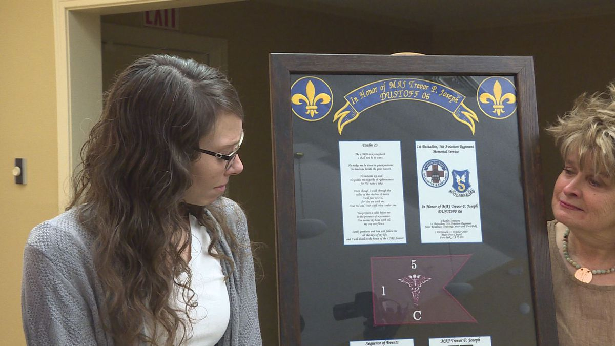 Erin Joseph stands next to her husband's plaque, (Maj. Trevor Joseph) after the city added his plaque to the Wall of Heroes | KALB