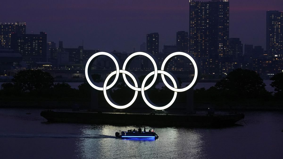 In this June 3, 2020, photo, the Olympic rings float in the water at sunset in the Odaiba...