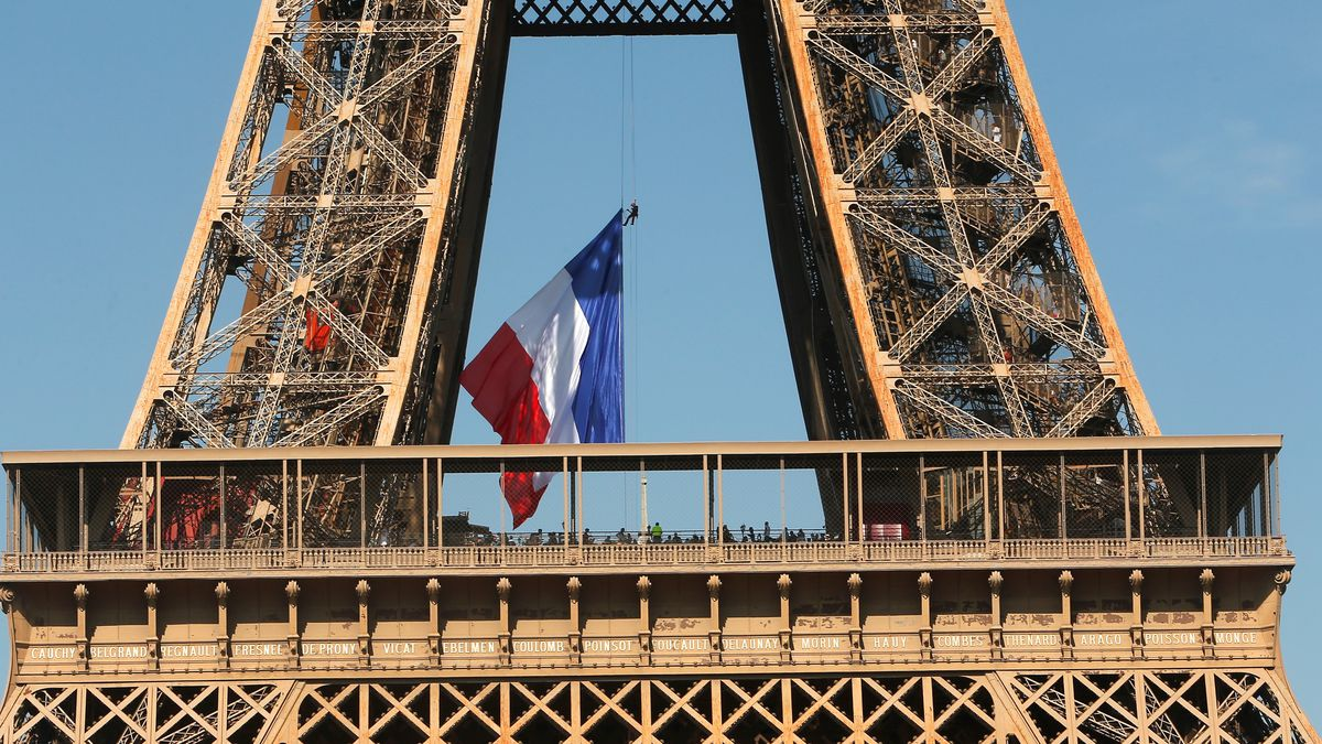 A French firefighter adjusts the French flag on the Eiffel Tower, in Paris, Sunday, Aug. 25,...
