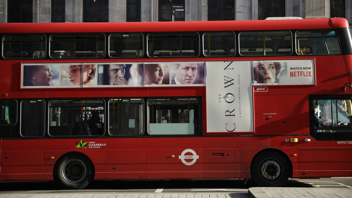 """A traditional double decker red bus with an advertisement for """"The Crown"""" drives through..."""