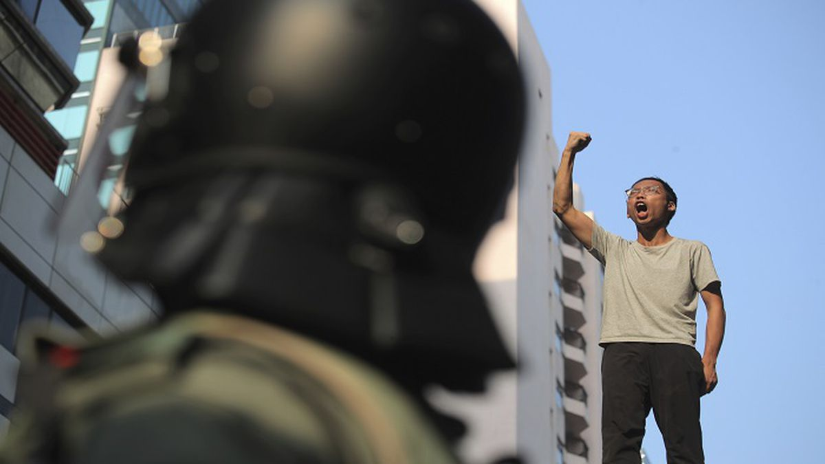 A man on top of a bridge raises his fist shouting slogans as he's stopped by police while trying to escape the Hong Kong Polytechnic University campus in Hong Kong, Monday, Nov. 18, 2019. Hong Kong police using tear gas and rubber bullets fought off protesters Monday as they tried to break through a police cordon that is trapping hundreds of them on a university campus. (AP Photo/Kin Cheung)