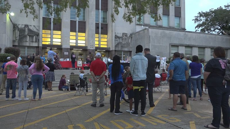 A crowd gathers around the Rapides Parish Courthouse for a candlelight vigil to remember the...