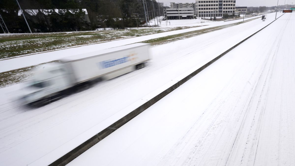 An 18-wheeler speeds along an ice covered Interstate 55 in north Jackson, Miss., Monday, Feb....