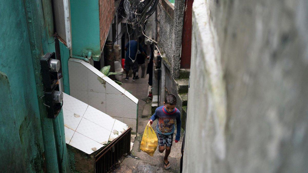 A boy carries a bag with bread as he walks up an alley in the Rocinha slum of Rio de Janeiro,...