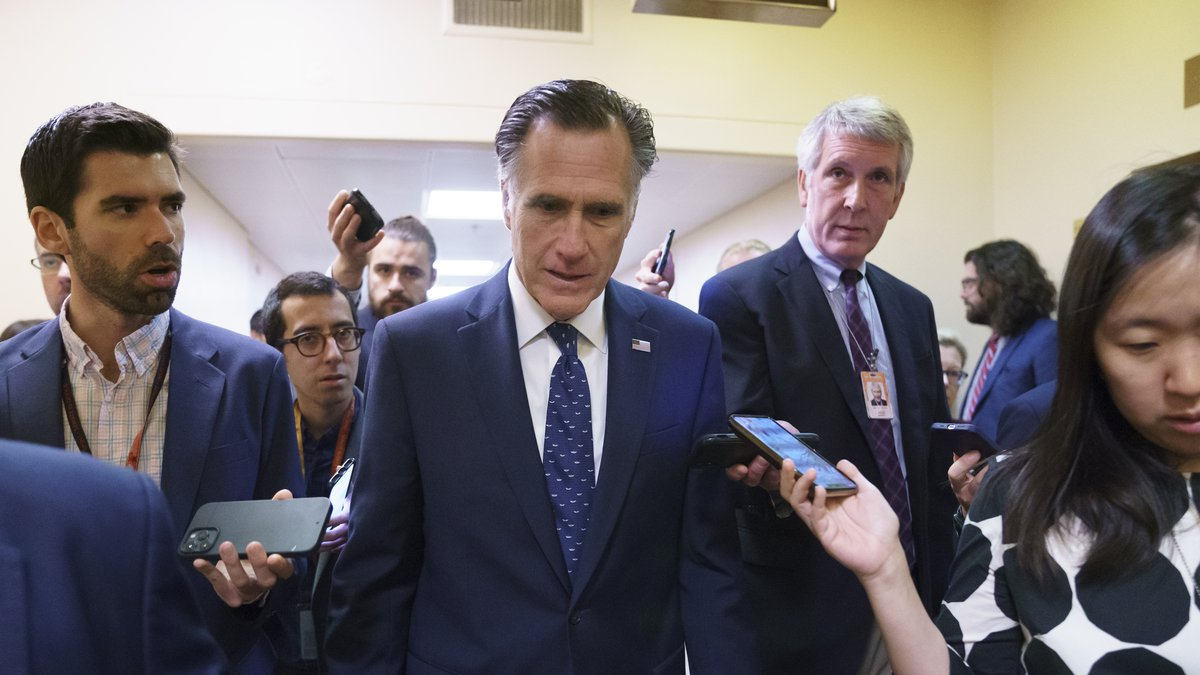 Sen. Mitt Romney, R-Utah, is surrounded by reporters as he walks to the Senate chamber for...
