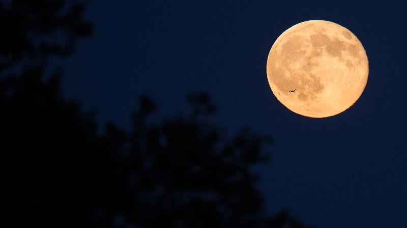A plane is seen flying in front of a full moon in July 2015 in Arlington, Va.