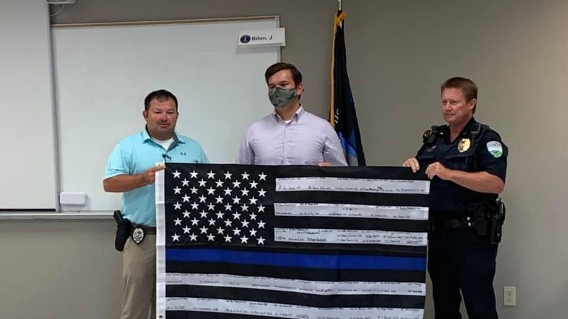 """Local officers present a student with a """"Thin Blue Line"""" flag after his parking spot was..."""