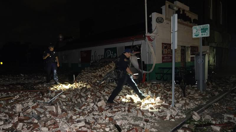 Police look through debris after a building collapsed from the effects of Hurricane Ida,...