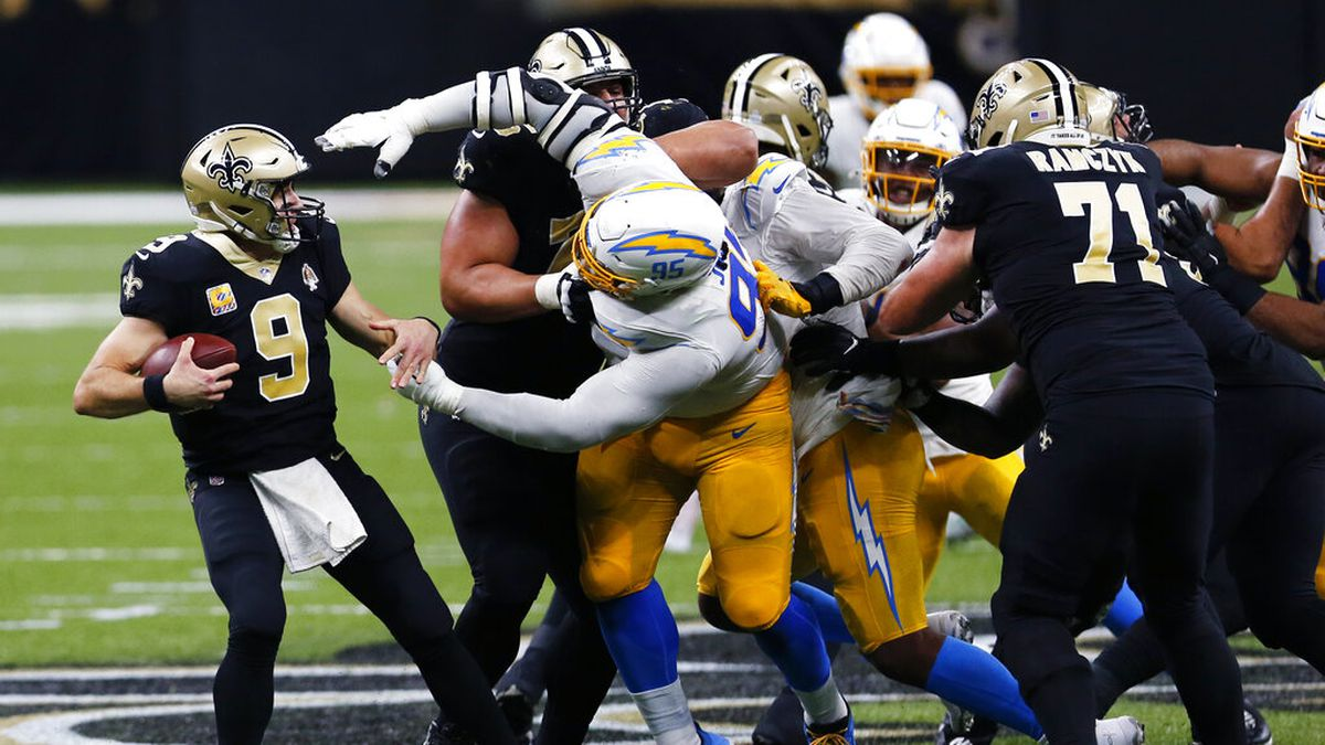New Orleans Saints quarterback Drew Brees (9) tries to avoid the sack by Los Angeles Chargers defensive tackle Linval Joseph (95) in the second half of an NFL football game in New Orleans, Monday, Oct. 12, 2020.
