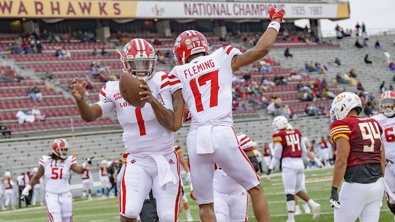 Louisiana-Lafayette quarterback Levi Lewis (1) celebrates a touchdown with wide receiver Dontae...