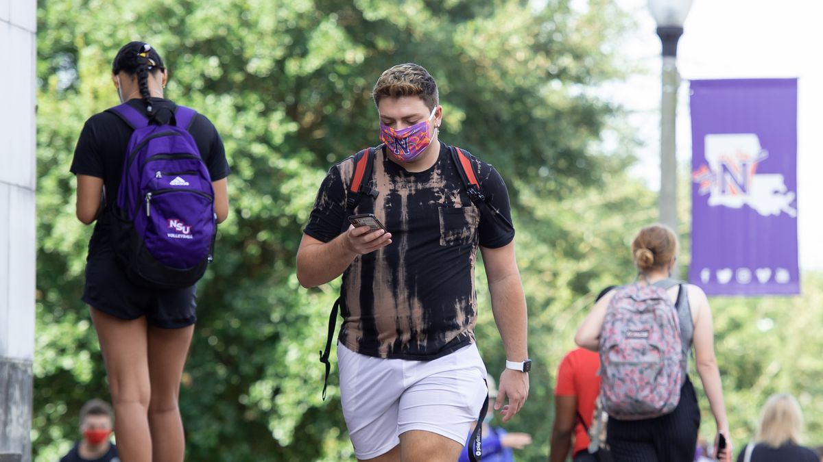 Student on NSU's campus wearing a mask.