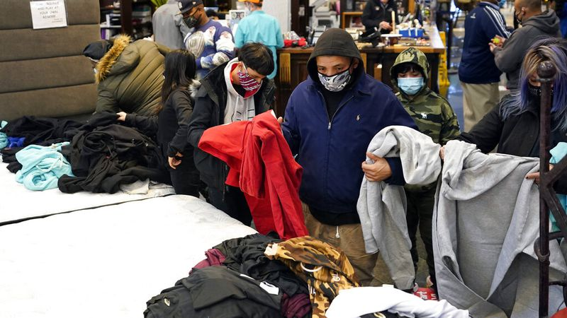 People select shirts and sweatshirts being given away at a Gallery Furniture store after the...