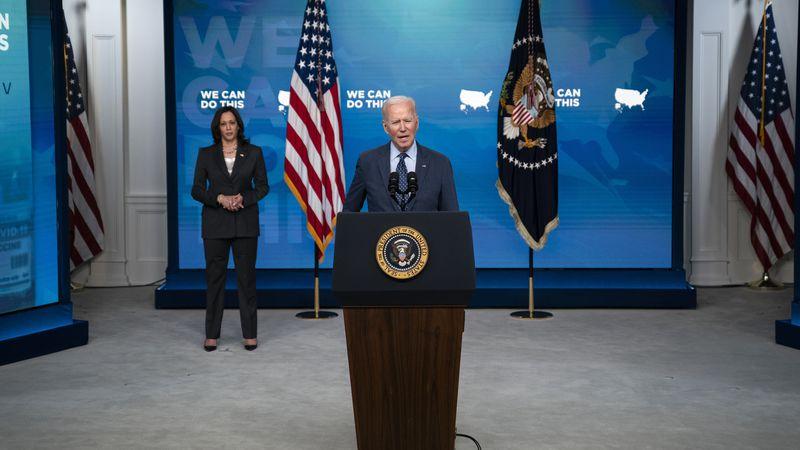 Vice President Kamala Harris listens as President Joe Biden speaks about the COVID-19...
