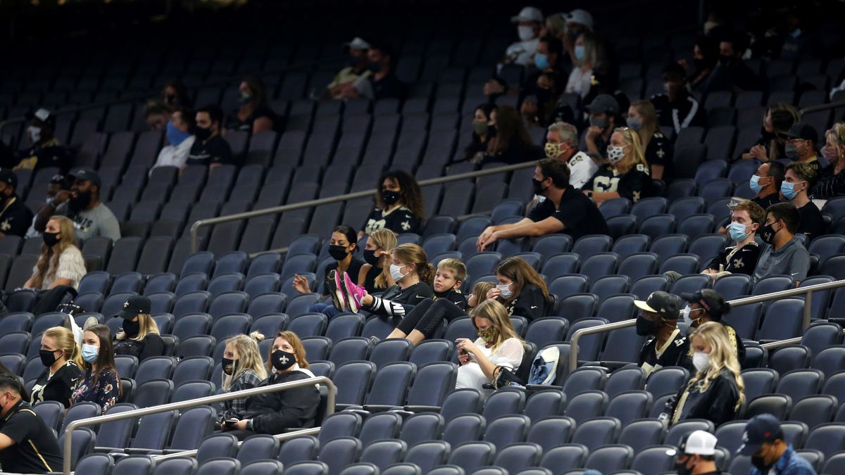 Family members of the New Orleans Saints sit in the stands wearing masks and exercising social...