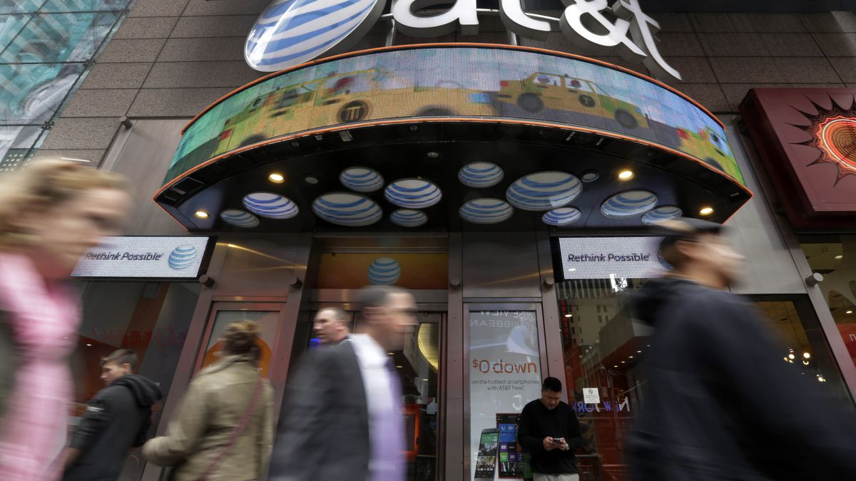 FILE - In this Oct. 21, 2014 file photo, people pass an AT&T store in New York's Times Square....