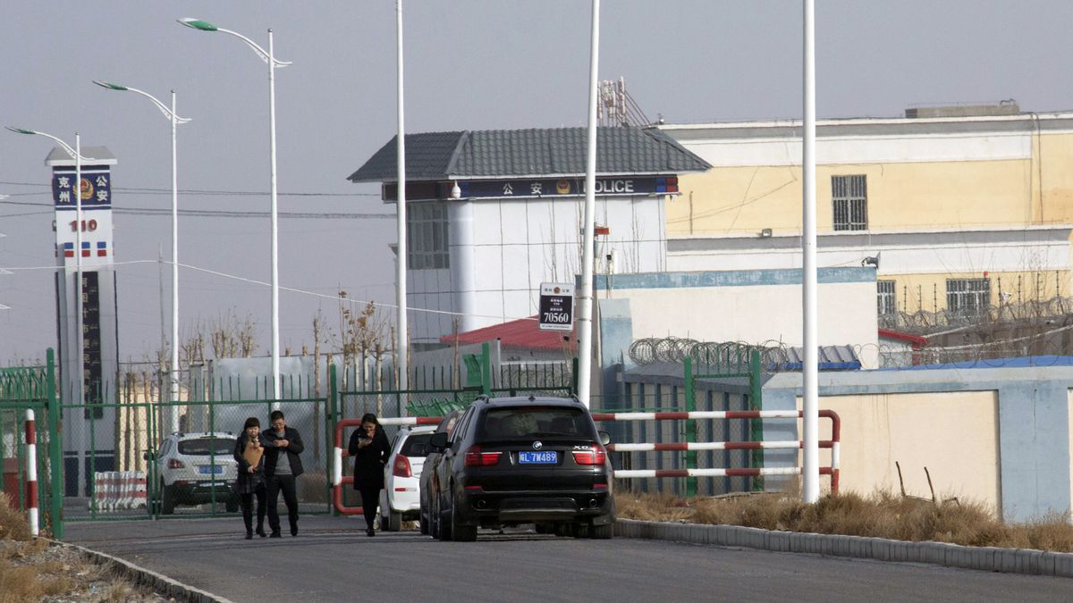 In this Dec. 3, 2018 file photo, people walk by a police station by the front gate of the Artux...