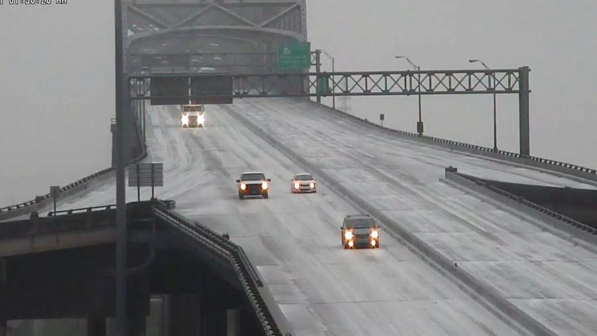 Several vehicles traveling on an iced-over portion of I-10 at the Mississippi River Bridge in...