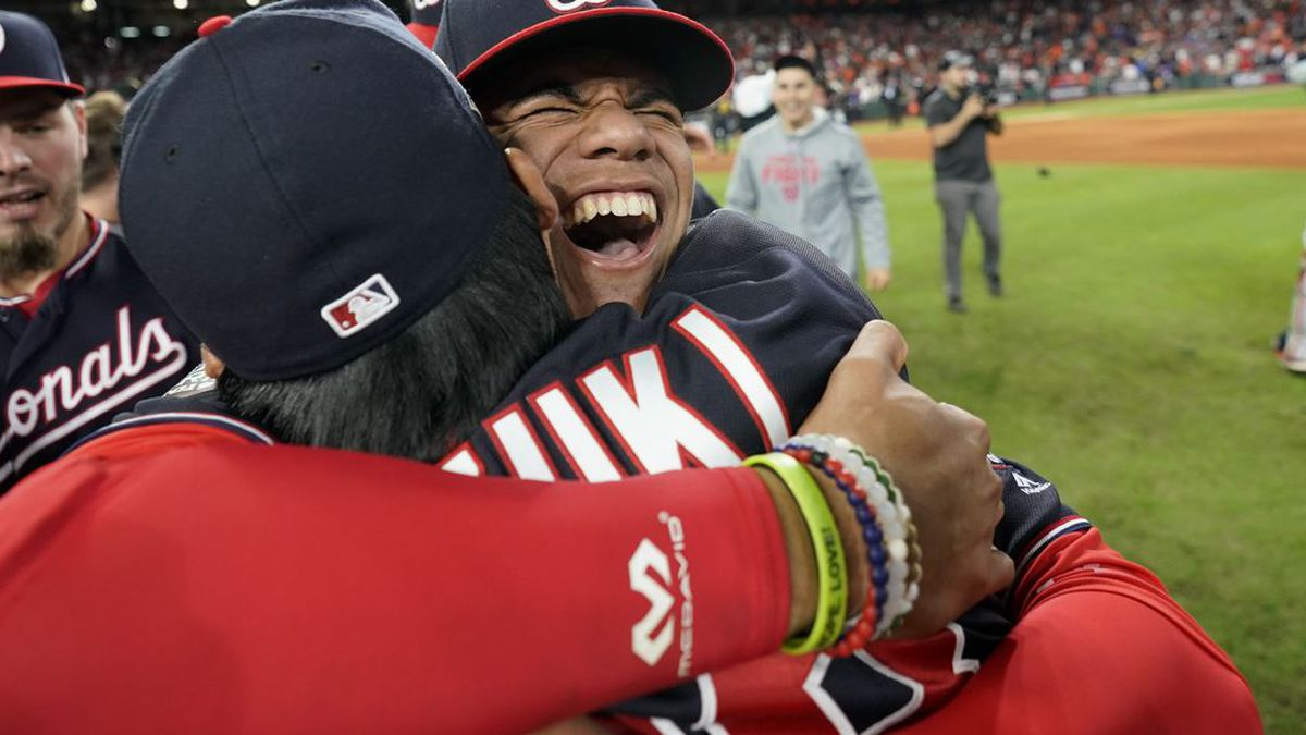Washington Nationals left fielder Juan Soto, right, hugs catcher Kurt Suzuki after Game 7 of the baseball World Series against the Houston Astros Wednesday, Oct. 30, 2019, in Houston. The Nationals won 6-2 to win the series. (Source: AP Photo/David J. Phillip)
