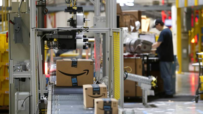 FILE- In this Aug. 3, 2017, file photo, packages pass through a scanner at an Amazon...