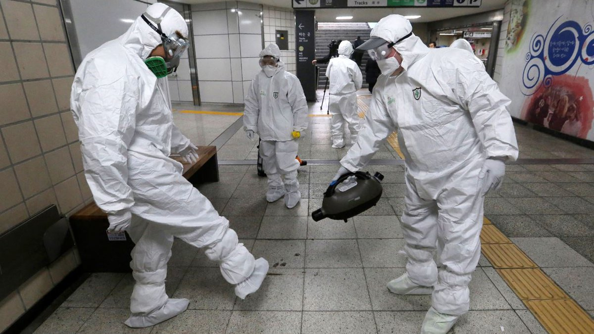 Workers wearing protective gear help clean each other's suits after disinfecting as a...