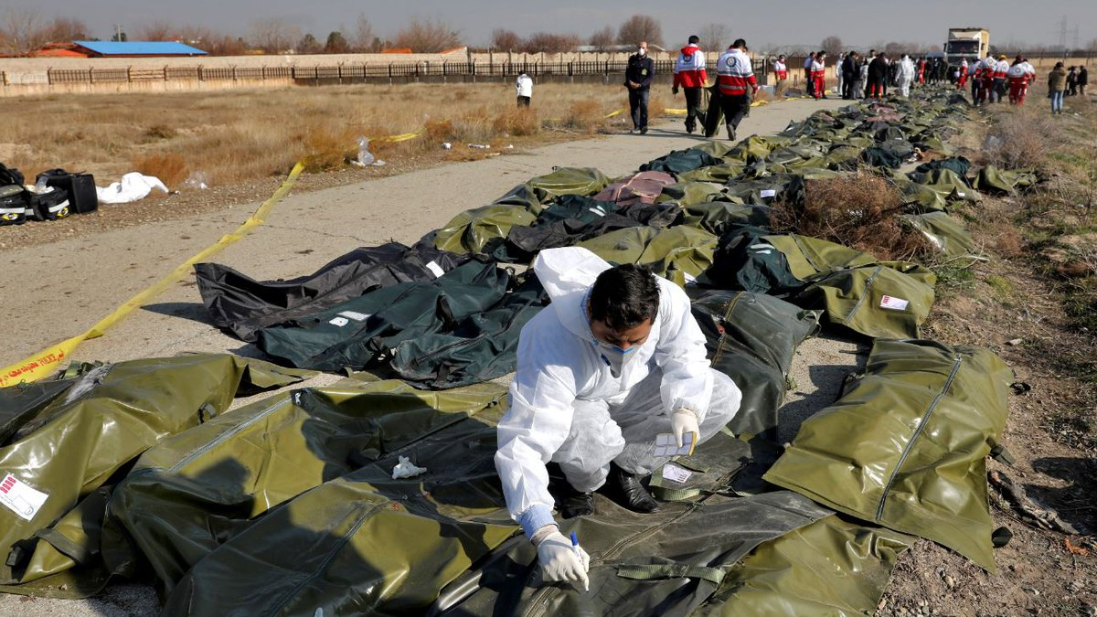 A forensic investigator works at the scene of a Ukrainian plane crash as bodies of the victims...