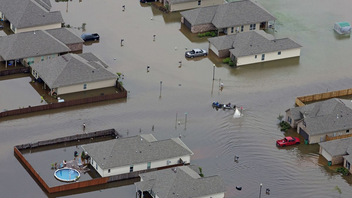 FILE- In this Saturday, Aug. 13, 2016 file aerial photo, a boat motors between flooded homes after heavy rains inundating the region, in Hammond, La. | Photo Source: AP Photo / Max Becherer