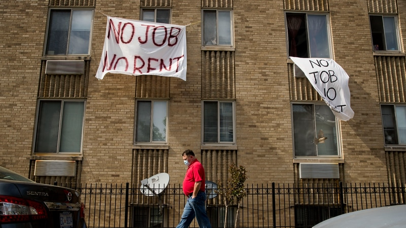 "FILE - In this May 20, 2020, file photo, signs that read ""No Job No Rent"" hang from the windows..."